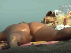 blonde-sunbathes-nude-on-the-beach-and-shows-a-little-snatc