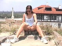 long-legged chick spreads her legs to rub her twat outdoor