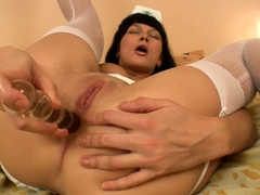Naughty nurse stuffing her ass with a glass dildo